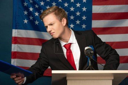 Photo pour Homme insatisfait regardant presse-papiers sur tribune sur fond de drapeau américain - image libre de droit