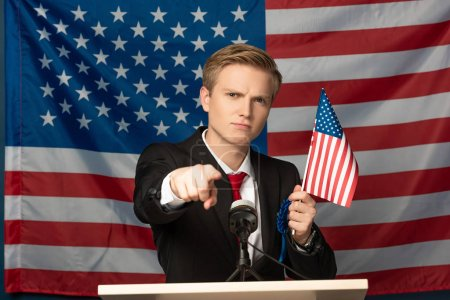 displeased man pointing with finger at camera on tribune on american flag background