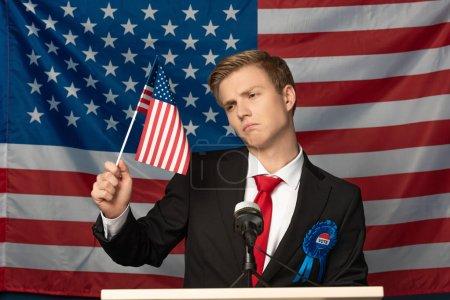 Photo pour Homme mécontent sur tribune et tenant drapeau américain - image libre de droit