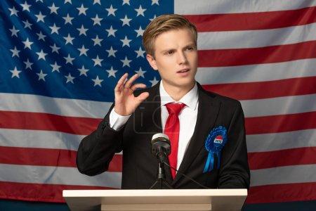 Photo pour Homme émotionnel sur tribune pendant le discours sur fond de drapeau américain - image libre de droit