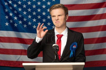 Photo pour Displeased emotional man on tribune on american flag background - image libre de droit