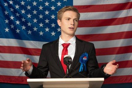Photo pour Homme parlant sur tribune sur fond de drapeau américain - image libre de droit