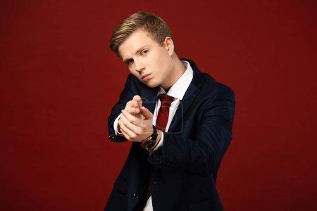confident man showing hand gun gesture on red background