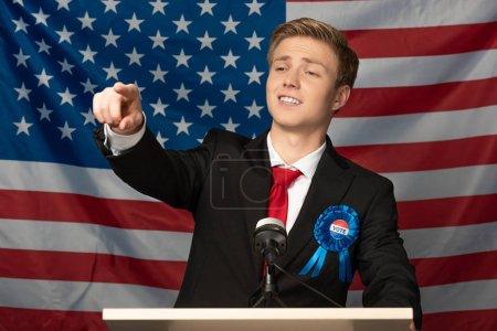 Photo pour Homme confiant pointant du doigt sur tribune sur fond de drapeau américain - image libre de droit