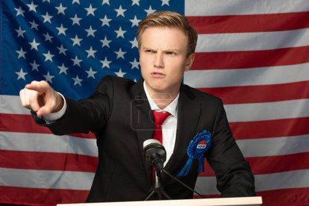 Photo pour Homme en colère pointant du doigt sur tribune sur fond de drapeau américain - image libre de droit