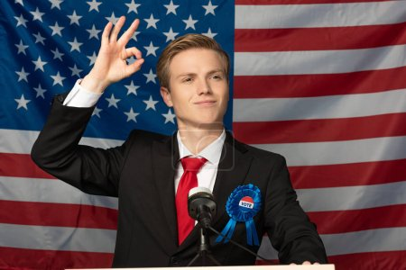 smiling man showing ok sign while on tribune on american flag background