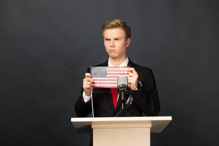 Photo pour Homme émotionnel en colère sur tribune avec drapeau américain sur fond noir - image libre de droit