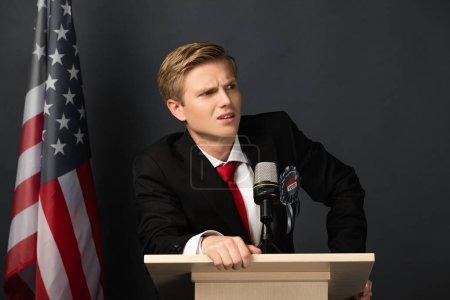 Photo pour Indigné homme émotionnel sur tribune avec drapeau américain sur fond noir - image libre de droit