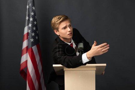 emotional man gesturing on tribune with american flag on black background