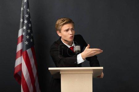 Photo pour Homme émotionnel geste sur tribune avec drapeau américain sur fond noir - image libre de droit