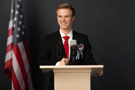 Photo pour Heureux homme émotionnel sur tribune avec drapeau américain sur fond noir - image libre de droit