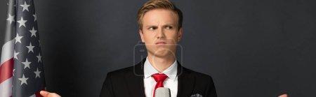 Photo pour Dissatisfied emotional man with american flag on black background - image libre de droit