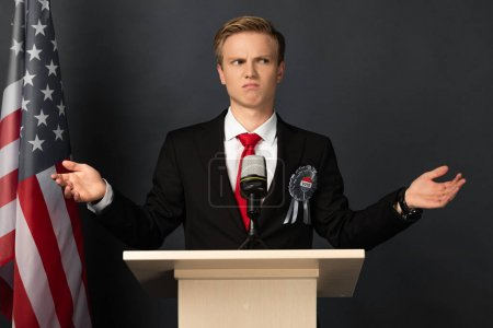 Photo pour Dissatisfied emotional man on tribune with american flag on black background - image libre de droit