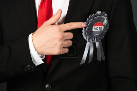 Photo pour Crochet vue d'un homme en costume noir pointé du doigt à l'insigne avec lettrage du vote - image libre de droit