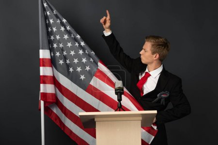 Photo pour Displeased emotional man with raised hand on tribune with american flag on black background - image libre de droit