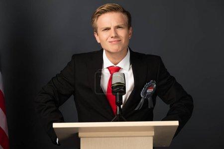 Photo pour Smiling emotional man on tribune on black background - image libre de droit