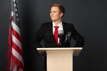 Photo pour Smiling emotional man on tribune with american flag on black background - image libre de droit