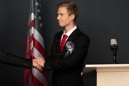 Photo pour Smiling emotional man shaking hand on tribune with american flag on black background - image libre de droit