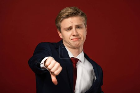 Photo pour Displeased man showing thumb down on red background - image libre de droit