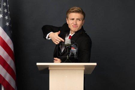 Photo pour Homme émotionnel pointant du doigt sur tribune avec drapeau américain sur fond noir - image libre de droit