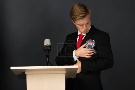 Photo pour Emotional man looking at badge on tribune on black background - image libre de droit