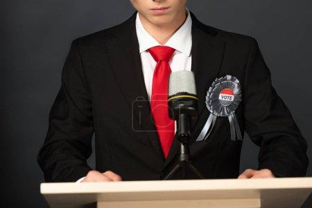 Photo pour Cropped view of man on tribune on black background - image libre de droit