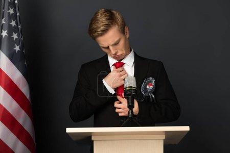 Photo pour Homme émotionnel touchant cravate sur tribune avec drapeau américain sur fond noir - image libre de droit