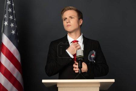 Photo pour Pensive man touching tie on tribune with american flag on black background - image libre de droit