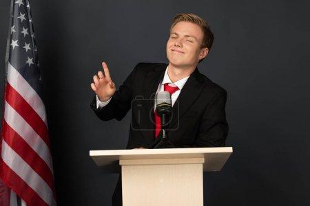 Photo pour Homme émotionnel souriant montrant geste d'idée sur tribune avec drapeau américain sur fond noir - image libre de droit