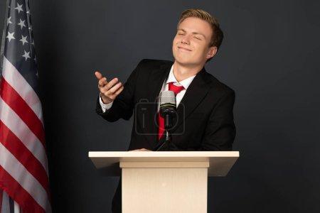 Photo pour Smiling emotional man gesturing on tribune with american flag on black background - image libre de droit