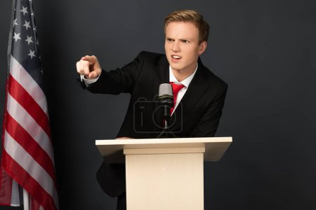 Photo pour Homme émotionnel en colère pointant du doigt sur tribune avec drapeau américain sur fond noir - image libre de droit