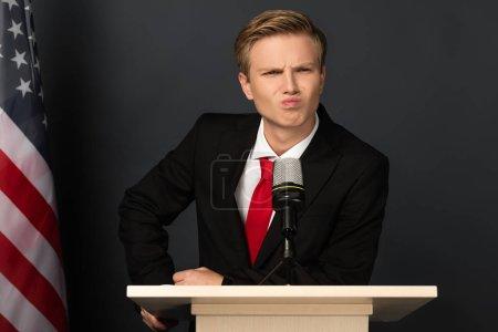 Photo pour Homme émotionnel grimaçant sur tribune avec drapeau américain sur fond noir - image libre de droit