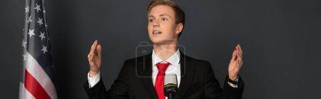 Photo pour Homme émotionnel parlant au microphone avec drapeau américain sur fond noir - image libre de droit