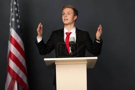 Photo pour Homme émotionnel parlant sur tribune avec drapeau américain sur fond noir - image libre de droit