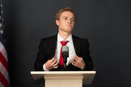 Photo pour Bouleversé émotionnel homme toucher veste sur tribune avec drapeau américain sur fond noir - image libre de droit