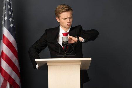 Photo pour Homme émotionnel regardant montre-bracelet sur tribune avec drapeau américain sur fond noir - image libre de droit
