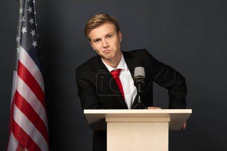 Photo pour Displeased emotional man on tribune with american flag on black background - image libre de droit