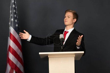 Photo pour Homme émotionnel gesticulant sur la tribune avec un drapeau américain sur fond noir - image libre de droit