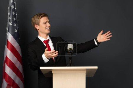 Photo pour Homme émotionnel parlant et gesticulant sur tribune avec drapeau américain sur fond noir - image libre de droit