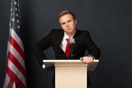 Photo for Sad emotional man on tribune with american flag on black background - Royalty Free Image