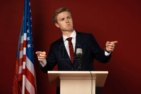 Photo pour Emotional man pointing with fingers on tribune near american flag on red background - image libre de droit