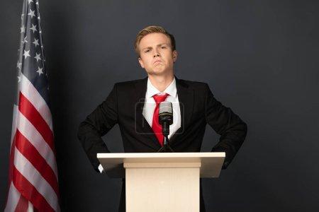 Photo pour Confiant homme émotionnel sur tribune avec drapeau américain sur fond noir - image libre de droit