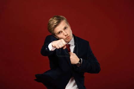 confident man showing fist on red background