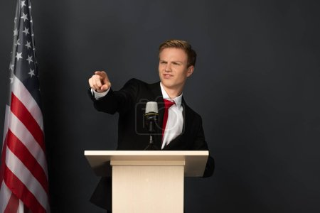 Photo for Emotional man pointing with finger at camera on tribune with american flag on black background - Royalty Free Image