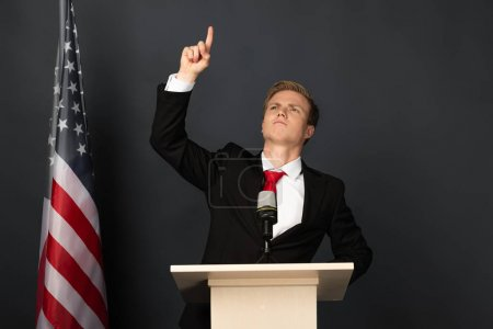emotional man pointing with finger upwards on tribune with american flag on black background
