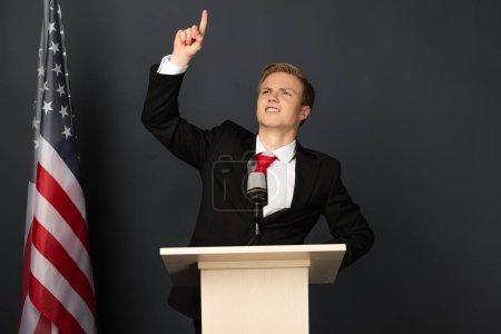 Foto de Hombre emocional que apunta con el dedo hacia arriba en la tribuna con bandera americana sobre fondo negro. - Imagen libre de derechos
