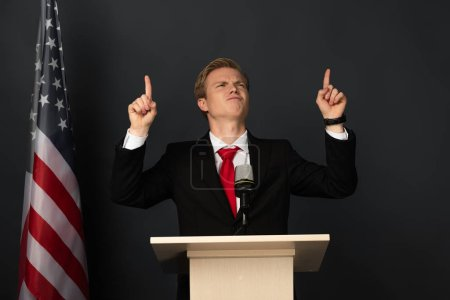 Photo pour Emotional man pointing with fingers upwards on tribune with american flag on black background - image libre de droit