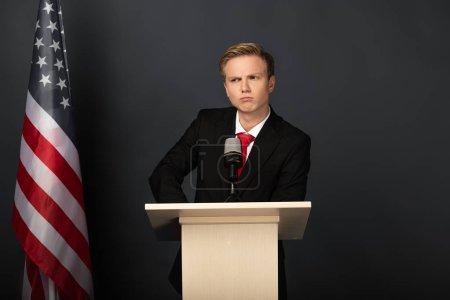 Photo pour Homme émotionnel sérieux sur tribune avec drapeau américain sur fond noir - image libre de droit
