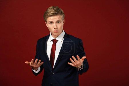 Photo pour Homme confus montrant geste haussant les épaules sur fond rouge - image libre de droit