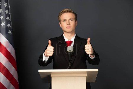 Foto de Emotivo hombre mostrando pulgares en la tribuna con bandera americana sobre fondo negro. - Imagen libre de derechos